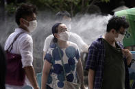 A woman wearing a protective mask to help curb the spread of the coronavirus cools down under a cooling mist spot at in Asakusa district Friday, Aug. 14, 2020, in Tokyo. The Japanese capital confirmed more than 380 coronavirus cases on Friday. (AP Photo/Eugene Hoshiko)