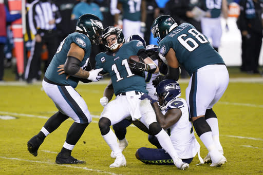 Philadelphia Eagles' Carson Wentz (11) is sacked by Seattle Seahawks' Benson Mayowa (95) during the second half of an NFL football game, Monday, Nov. 30, 2020, in Philadelphia. (AP Photo/Chris Szagola)