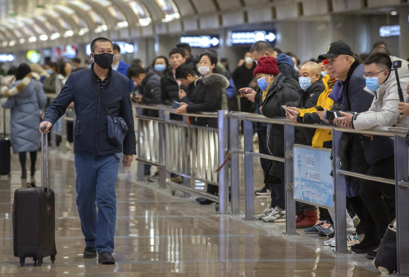 A traveler wearing a face mask walks into the arrivals area at Beijing Capital International Airport in Beijing, Thursday, Jan. 23, 2020. China closed off a city of more than 11 million people Thursday, halting transportation and warning against public gatherings, to try to stop the spread of a deadly new virus that has sickened hundreds and spread to other cities and countries in the Lunar New Year travel rush. (AP Photo/Mark Schiefelbein)