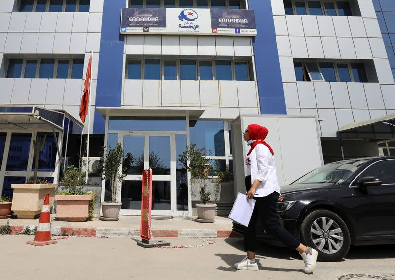 A woman walks past the building of the Islamist Ennahda party headquarters in Tunis