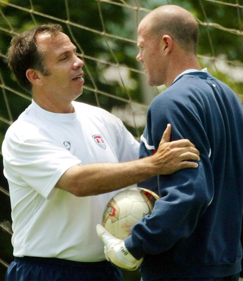 U.S. coach Bruce Arena (L) holds goalkeeper Brad Friedel during the team training in Seoul June 11, 2002. USA will play Poland on June 14 in its last match of the first round of the World Cup Finals. REUTERS/Shaun Best SB/JD