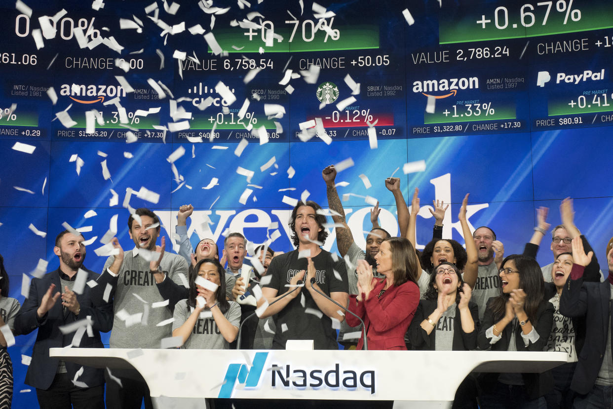 Adam Neumann, center, co-founder and CEO of WeWork, attends the opening bell ceremony at Nasdaq, Tuesday, Jan. 16, 2018, in New York. (AP Photo/Mark Lennihan)