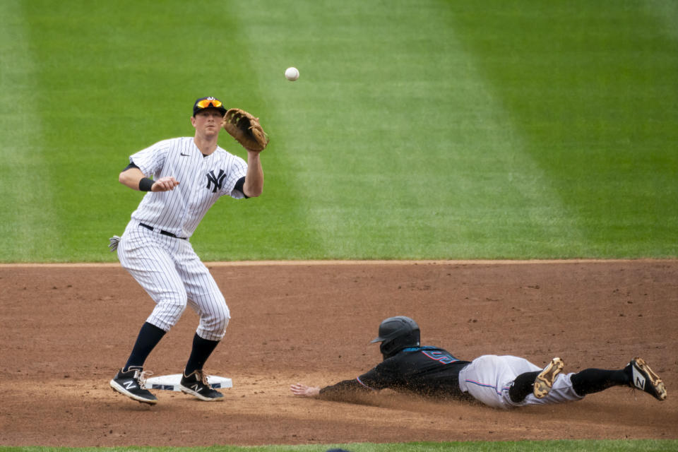 File-This Sept. 26, 2020, file photo shows Miami Marlins' Jon Berti stealing second base as New York Yankees second baseman DJ LeMahieu waits for the throw during the third inning of a baseball game at Yankee Stadium in New York. Houston Astros outfielder George Springer, LeMahieu, and Philadelphia catcher J.T. Realmuto were among just six free agents who received $18.9 million qualifying offers on Sunday, Nov. 1, 2020, from their former teams. Three right-handed pitchers also received the offers, Cincinnati's Trevor Bauer, the New York Mets' Marcus Stroman, and San Francisco's Kevin Gausman. (AP Photo/Corey Sipkin, File)