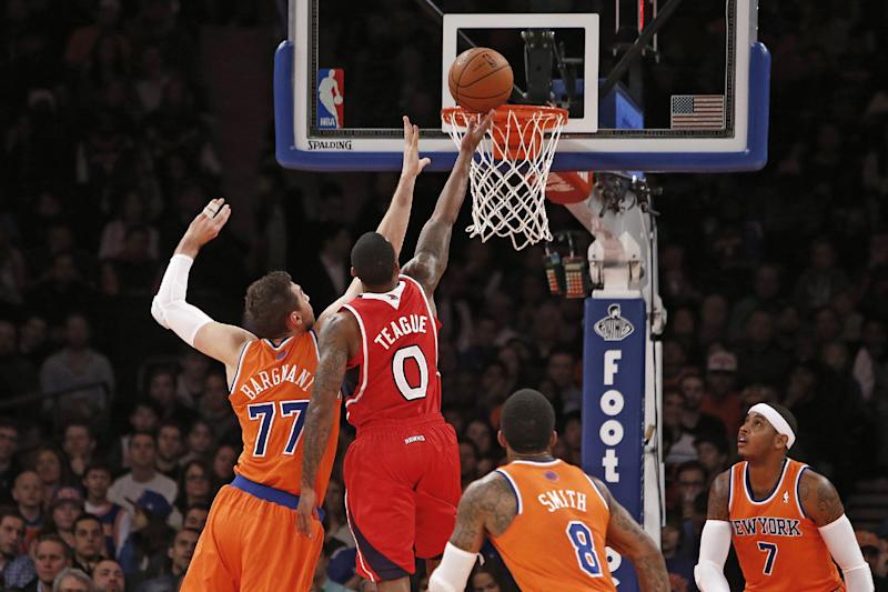 Atlanta Hawks' Jeff Teague (0) shoots against New York Knicks' Andrea Bargnani (77), of Italy, as J.R. Smith (8) and Carmelo Anthony (7) look on during the first half of an NBA basketball game Saturday, Nov. 16, 2013, in New York. (AP Photo/Jason DeCrow)