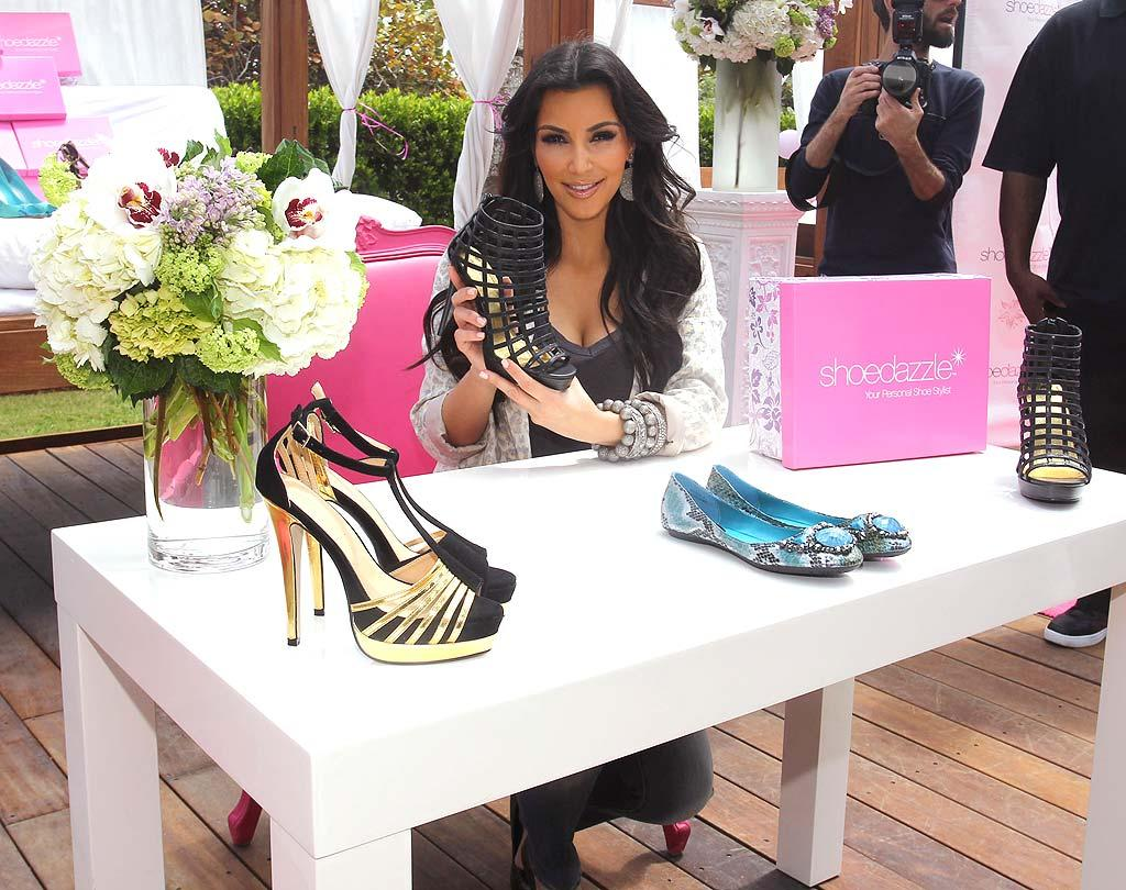 "<b>Build a Fashion Empire:</b> Apparently, all that posing paid off! In 2009, Kim co-founded the website ShoeDazzle, a shopping service that selects shoes and accessories for its clients. The savvy stunner added the venture to a fashion portfolio that already included the Dash boutique she co-owns with her sisters in Los Angeles. Since then, her business empire has grown to include clothing lines for Bebe and QVC, a jewelry collection, perfume, sunless tanner, and Dash stores in Miami and the Big Apple (which the siblings are documenting in additional reality shows, natch!). Brian Prahl/<a href=""http://www.splashnewsonline.com"" target=""new"">Splash News</a> - March 24, 2010"