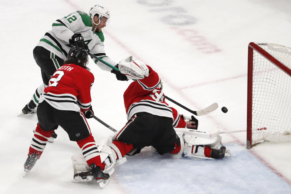 Dallas Stars center Radek Faksa (12) scores a goal past Chicago Blackhawks goaltender Kevin Lankinen (32) and Duncan Keith (2) during the third period of an NHL hockey game Tuesday, April 6, 2021, in Chicago. (AP Photo/Jeff Haynes)
