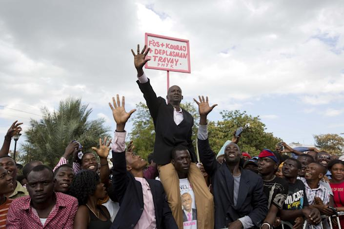 """A supporter of Haiti's President Jovenel Moise impersonates the new president, with a sign behind him that reads in Creole """"Energy plus encouragement plus movement plus work"""" during Moise's inauguration in Port-au-Prince, Haiti, Tuesday, Feb. 7, 2017. Moise was sworn-in as president for the next five years after a bruising two-year election cycle, inheriting a struggling economy and a deeply divided society. (AP Photo/Dieu Nalio Chery)"""