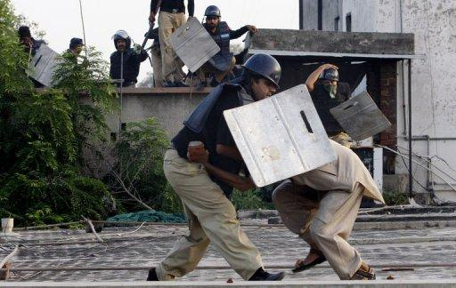 "A Pakistani policeman detains a demonstrator during a protest against the US-made film ""Innocence of Muslims"" in Lahore. Ties between Pakistan and the US are improving after hitting a low point, Pakistani Foreign Minister Hina Rabbani Khar insisted Friday, even as violent anti-US protests rocked her country"