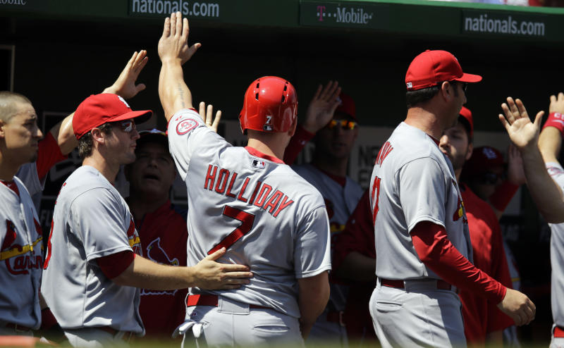 St. Louis Cardinals left fielder Matt Holliday (7) celebrates with his teammates after scoring during the first inning of a baseball game against the Washington Nationals at Nationals Park Wednesday, April 24, 2013, in Washington. (AP Photo/Alex Brandon)