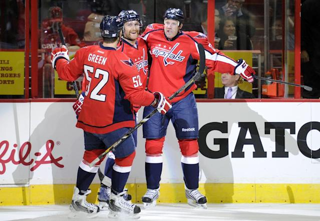 Washington Capitals left wing Jason Chimera, right, celebrates his goal with Karl Alzner, center, and Mike Green (52) against the Carolina Hurricanes during the first period an NHL hockey game, Thursday, Oct. 10, 2013, in Washington. (AP Photo/Nick Wass)