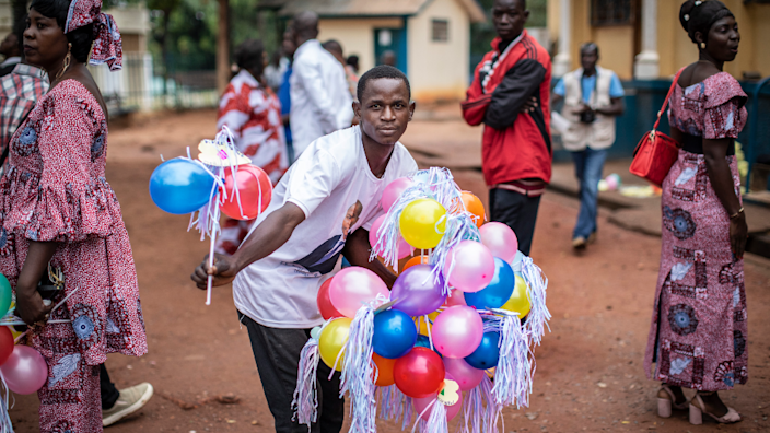 A man holds balloons for friends and family members during a wedding outside the mayor's office in Bangui, Central African Republic - Saturday 20 March 2021