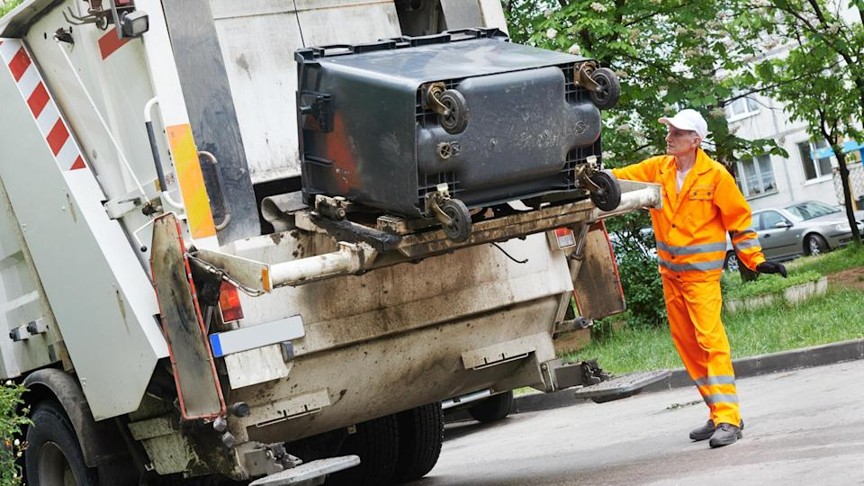 Worker of municipal recycling garbage collector truck loading waste and trash bin - Image.