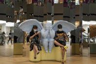 A couple wearing face masks to help curb the spread of the coronavirus sit on an angel statue browsing their smartphones at a shopping mall in Beijing, Sunday, June 6, 2021. (AP Photo/Andy Wong)
