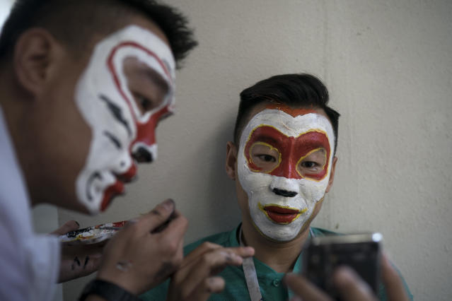 FILE - In this Wednesday, June 20, 2018 file photo, soccer fans from China check their face paint on a smartphone screen before the group B match between Portugal and Morocco at the 2018 soccer World Cup in the Luzhniki Stadium in Moscow, Russia, Wednesday, June 20, 2018. (AP Photo/Felipe Dana)
