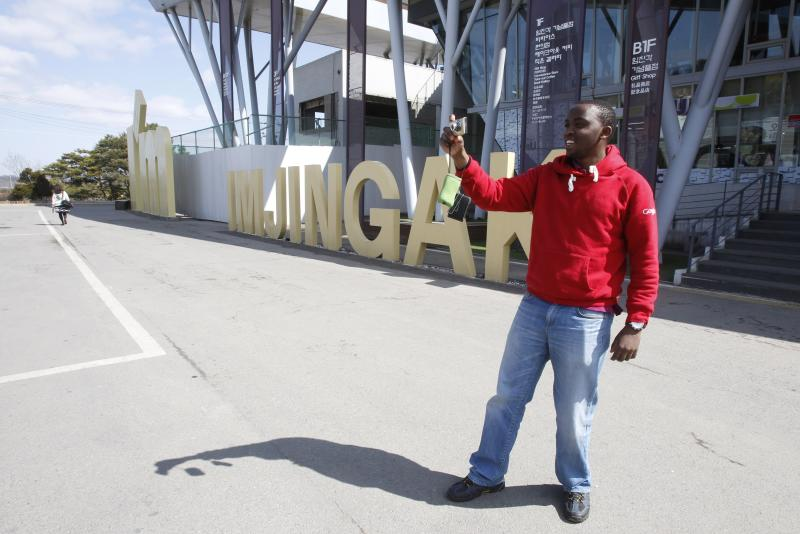 Hiram Macharia, a 25-year-old Kenyan, takes a picture at Imjingak Pavilion in Paju near the demilitarized zone between the two Koreas, South Korea,Thursday, March 14, 2013. Busloads of tourists still show up to gawk at the world's most heavily fortified border, even as governments on both sides threaten to reduce each other to rubble. (AP Photo/Ahn Young-joon)