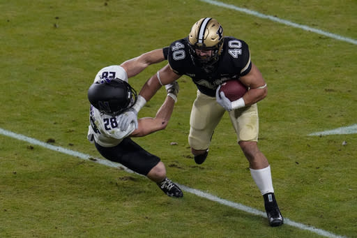 Purdue running back Zander Horvath (40) pushes off the tackle of Northwestern linebacker Chris Bergin (28) during the first half of an NCAA college football game in West Lafayette, Ind., Saturday, Nov. 14, 2020. (AP Photo/Michael Conroy)