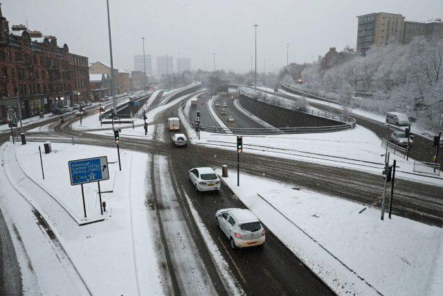 Cars drive in the snow-covered Charing Cross area of Glasgow (Andrew Milligan/PA)