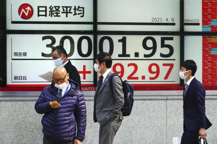 People wearing protective masks stand in front of an electronic stock board showing Japan's Nikkei 225 index at a securities firm in Tokyo Friday, April 9, 2021. Shares fell Friday in most Asian markets after China reported a stronger than expected rise in prices that could prompt authorities to act to cool inflation. (AP Photo/Eugene Hoshiko)