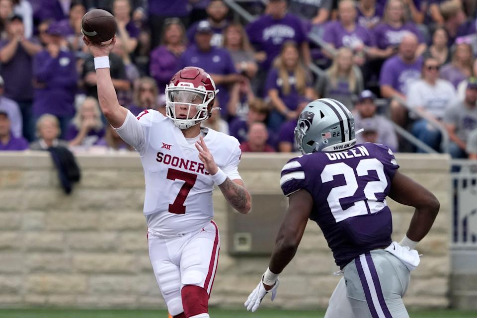 Oklahoma quarterback Spencer Rattler (7) passes to a teammate while chased by Kansas State linebacker Daniel Green (22) during the first half in Manhattan, Kan.