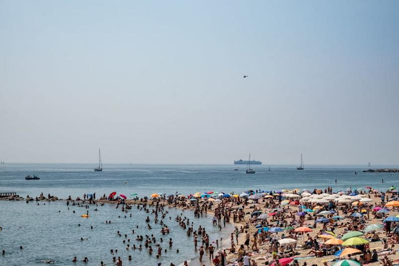 Tourists and locals gather on a beach in Barcelona during a heatwave. Locals say waves of tourism, especially from cruise ships, push up property prices and don't benefit locals. (Photo by Paco Freire/SOPA Images/LightRocket via Getty Images.)