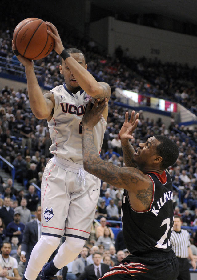 Connecticut's Shabazz Napier (13) and Cincinnati's Sean Kilpatrick (23) fight for a rebound during the first half of an NCAA college basketball game in Hartford, Conn., Sunday, March 1, 2014. (AP Photo/Fred Beckham)