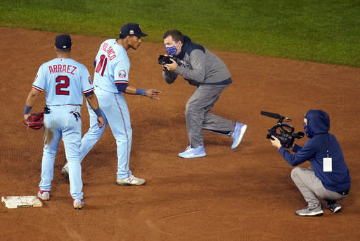 Minnesota Twins shortstop Jorge Polanco (11) plays to the cameras after the Twins defeated the Cincinnati Reds 7-3 in a baseball game Saturday, Sept. 26, 2020, in Minneapolis. (AP Photo/Jim Mone)