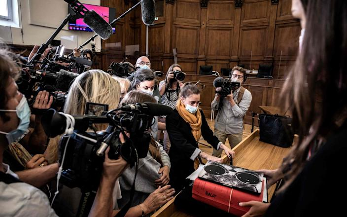 Valerie Bacot arrives in court flanked by her family and surrounded by journalists - JEFF PACHOUD/AFP via Getty Images