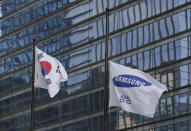 A flag of Samsung flutters at half-mast next to the South Korean national flag outside of Samsung's Seocho office building in Seoul, South Korea, Wednesday, Oct. 28, 2020. Lee Kun-Hee, late Samsung Electronics chairman who transformed the small television maker into a global giant of consumer electronics but whose leadership was also marred by corruption convictions, died on Sunday at the age of 78. (AP Photo/Lee Jin-man)