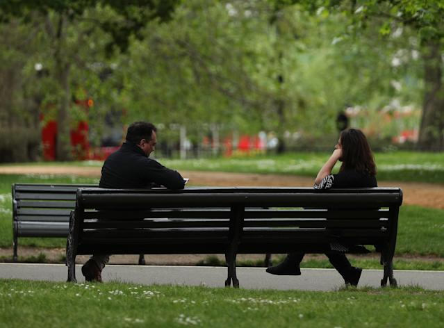 People observing social distancing on a bench in Hyde Park, London. (AP)