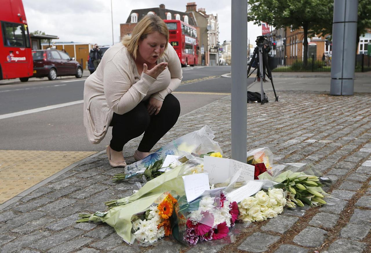 A woman blows a kiss as she lays a floral tribute in memory of the victim outside the Royal Artillery Barracks near the scene of a terror attack in Woolwich, southeast London, Thursday, May 23, 2013. A member of armed forces was attacked and killed by two men on Wednesday. (AP Photo/Sang Tan)