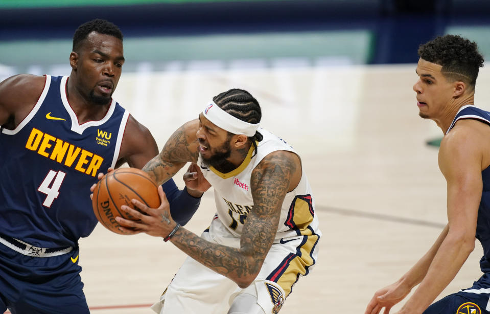 New Orleans Pelicans forward Brandon Ingram, center, drives to the rim between Denver Nuggets forwards Paul Millsap, left, and Michael Porter Jr. in the second half of an NBA basketball game Sunday, March 21, 2021, in Denver. The Pelicans won 113-108. (AP Photo/David Zalubowski)