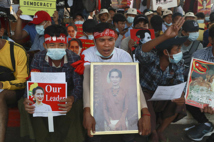 Protesters display images of deposed Myanmar leader Aung San Suu Kyi as they take part in a demonstration against the military coup in Yangon, Myanmar, Friday, Feb. 26, 2021. Security forces in Myanmar's largest city on Friday fired warning shots and beat truncheons against their shields while moving to disperse more than 1,000 anti-coup protesters. (AP Photo)
