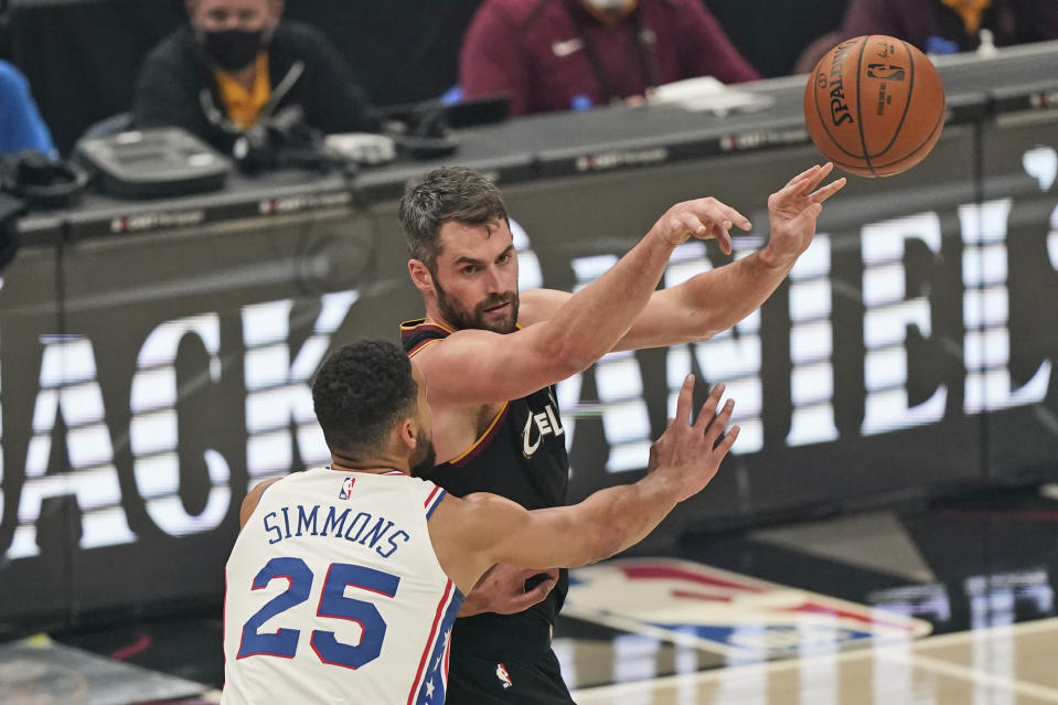 Cleveland Cavaliers' Kevin Love, right, passes against Philadelphia 76ers' Ben Simmons in the first half of an NBA basketball game, Sunday, Dec. 27, 2020, in Cleveland. (AP Photo/Tony Dejak)
