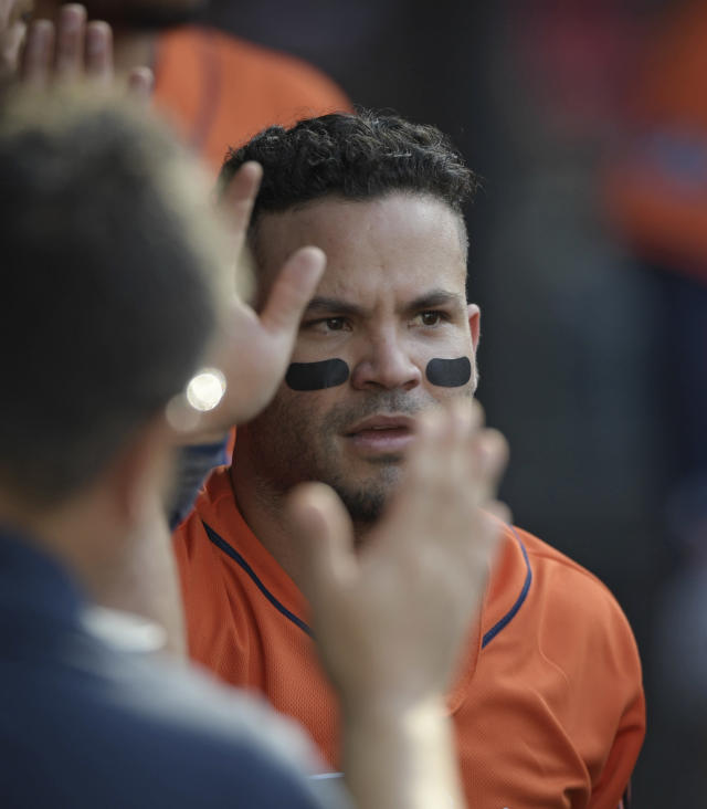 Houston Astros' Jose Altuve is congratulated by teammates after scoring in the seventh inning during Game 3 of a baseball American League Division Series against the Cleveland Indians, Monday, Oct. 8, 2018, in Cleveland. (AP Photo/David Dermer)