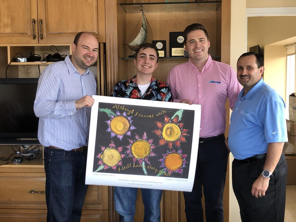 Gabriel Donovan (second from left) holds up his Adirondack Lilly design alongside the men from Spectrum Designs and the Center for Disability Services. (Photo courtesy of Maureen O'Brien)