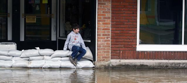 <p>A boy sit on sand bag's along Second St in Aurora, Indiana on Sunday, Feb. 25, 2018. (Photo: Ernest Coleman via ZUMA Wire) </p>