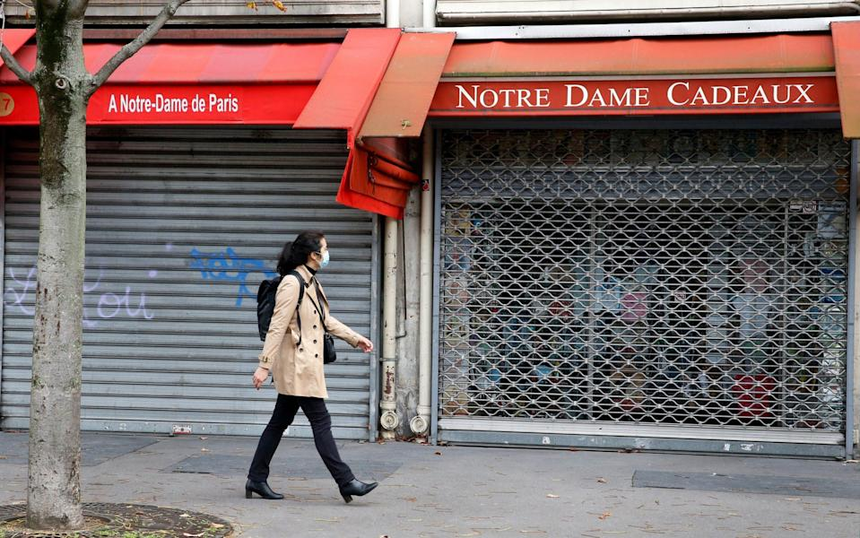 A woman walks past a closed shop in Paris - Chesnot
