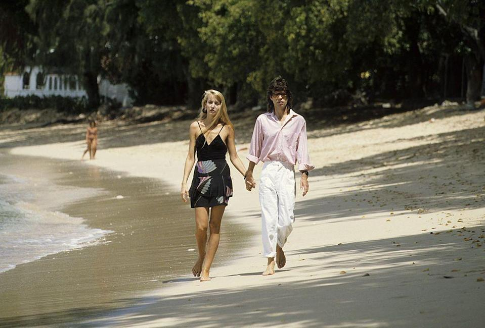 <p>Mick Jagger and Jerry Hall walk along a beach in Barbados. </p><p>Other celebrity visitors this year: Queen Elizabeth II.<br></p>