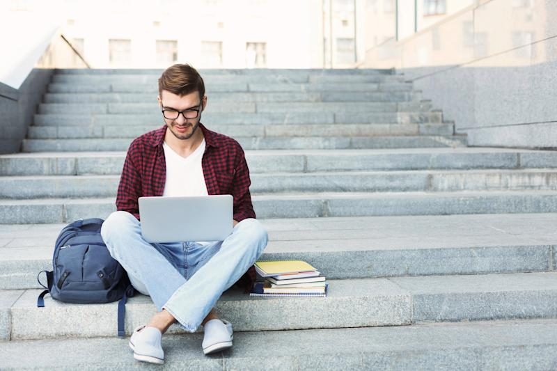 Young man on laptop sitting on steps