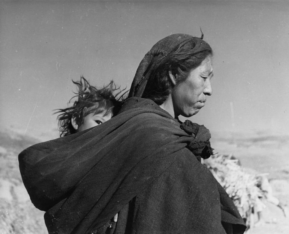 A Bolivian Indian mother carries her baby in a papoose.