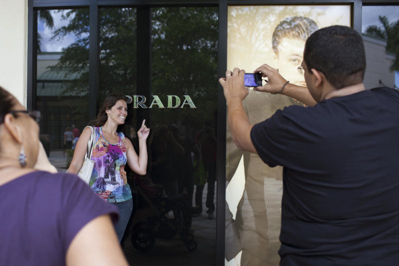 In this March 6, 2012 photo, Milena Rangel, from Macae, Brazil, poses for a photo taken by her husband Vanderson Rangel as they shop at the Sawgrass Mills mall in Fort Lauderdale, Florida. Brazilian travelers spend more per capita than any other visitors to the U.S. (AP Photo/Felipe Dana)