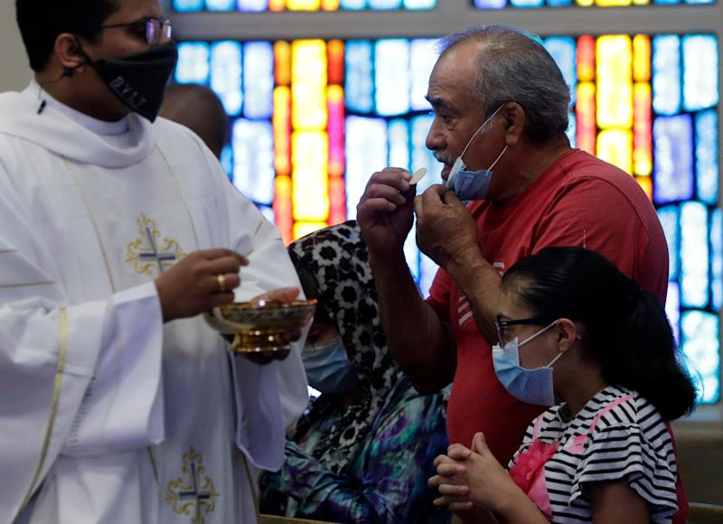 The Rev. Praveen Lakkisettit, left, wears a face mask as he delivers communion to parishioners during an in-person Mass at Christ the King Catholic Church in San Antonio, Tuesday, May 19, 2020.  (Photo: ASSOCIATED PRESS)