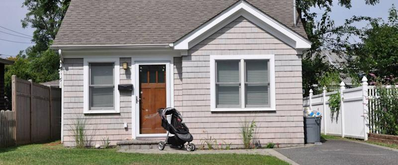 Suburban Bungalow Home with Baby Carriage Parked on Front Yard Lawn Sunny Residential Neighborhood House USA
