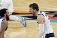 Dallas Mavericks guard Luka Doncic, right, celebrates a score against the San Antonio Spurs with Jalen Brunson (13) during the second half of an NBA basketball game in San Antonio, Friday, Jan. 22, 2021. (AP Photo/Eric Gay)