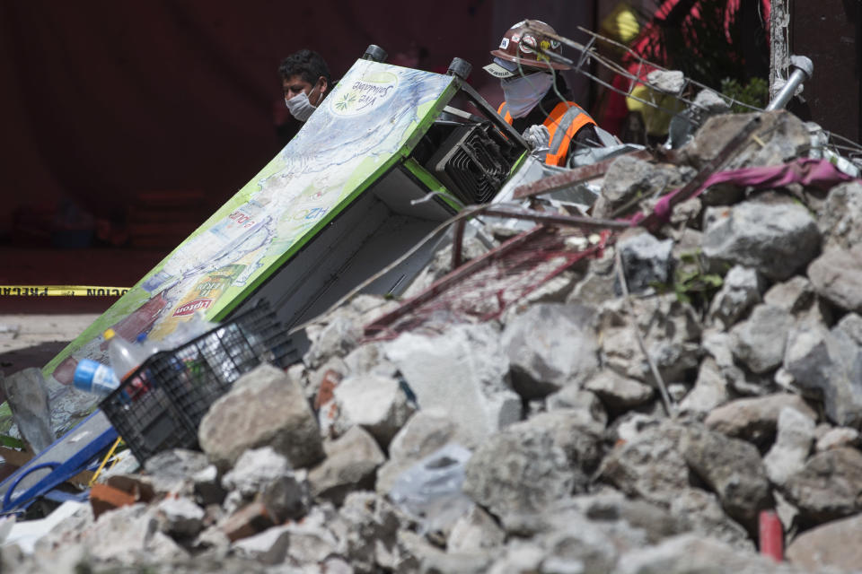 <p>Rescues workers walk past rubble in San Gregorio Atlapulco, Mexico, Friday, Sept. 22, 2017. Mexican officials are promising to keep up the search for survivors as rescue operations stretch into a fourth day following Tuesday's major earthquake that devastated Mexico City and nearby states. (AP Photo/Moises Castillo) </p>