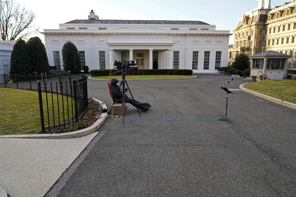 A cameraman waits by an unused microphone stand outside the West Wing at the White House, Tuesday, Jan. 19, 2021, in Washington. On President Donald Trump's last full day in office, there was an eerie quiet, with no public events scheduled, his last event being Jan. 12, seven days earlier. (AP Photo/Gerald Herbert)