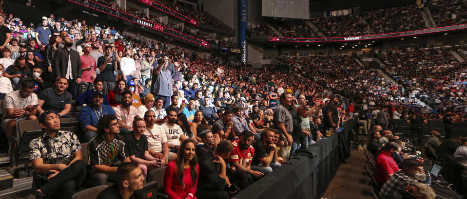 Fans attend a UFC 261 mixed martial arts event Saturday, April 24, 2021, in Jacksonville, Fla. The sold-out event touted as the first full-capacity sporting event held indoors in more than a year drew a star-studded crowd. (AP Photo/Gary McCullough)