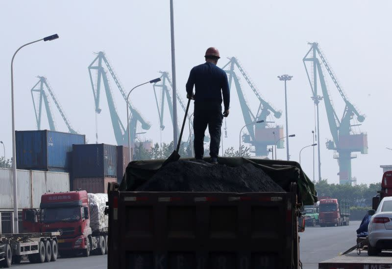 FILE PHOTO: A labourer loads coal in a truck next to containers outside a logistics center near Tianjin Port