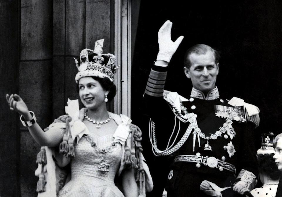 File photo dated 02/06/1953 of Queen Elizabeth II wearing the Imperial State Crown, and the Duke of Edinburgh, in the uniform of Admiral of the Fleet, waving from the balcony of Buckingham Palace after the Queen's Coronation. The Royal couple will celebrate their platinum wedding anniversary on November 20.
