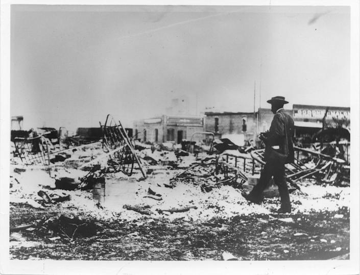 An African American photographer  looking at the ruins of the Midway Hotel in Tulsa.